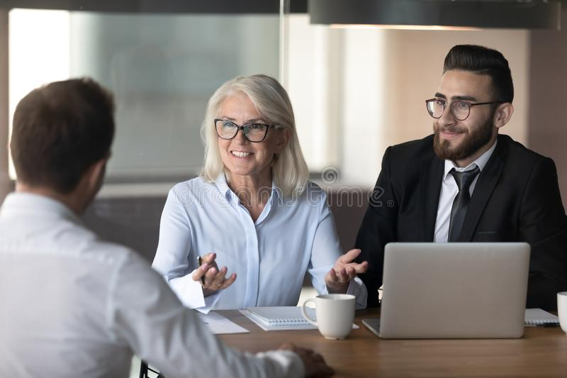Smiling hr managers holding interview with good job applicant. Smiling hr managers holding interview with job applicant, satisfied recruiters, mature royalty free stock photo