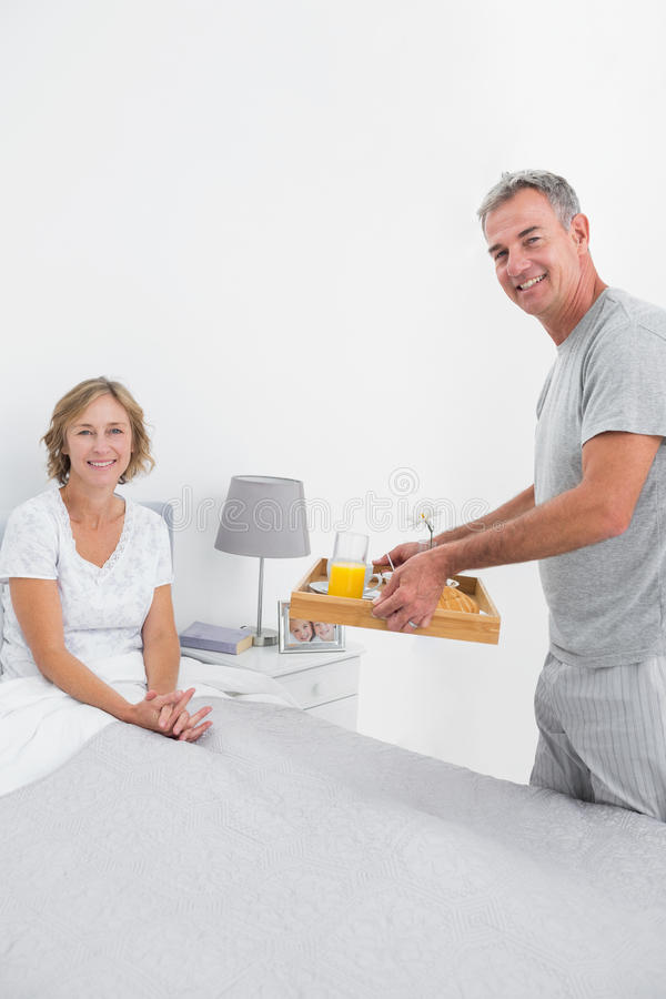 Smiling husband bringing breakfast in bed to wife