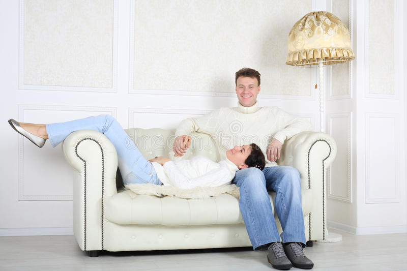 Smiling husband sits on white sofa and his wife lies. Smiling husband sits on white leather sofa and his wife lies on his knees at home stock image