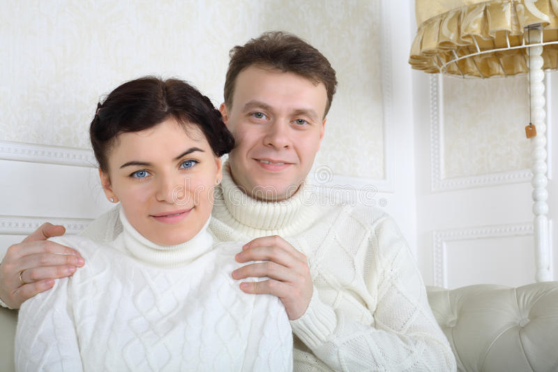 Smiling husband in white sweaters hugs wife shoulders. On white sofa at home stock image