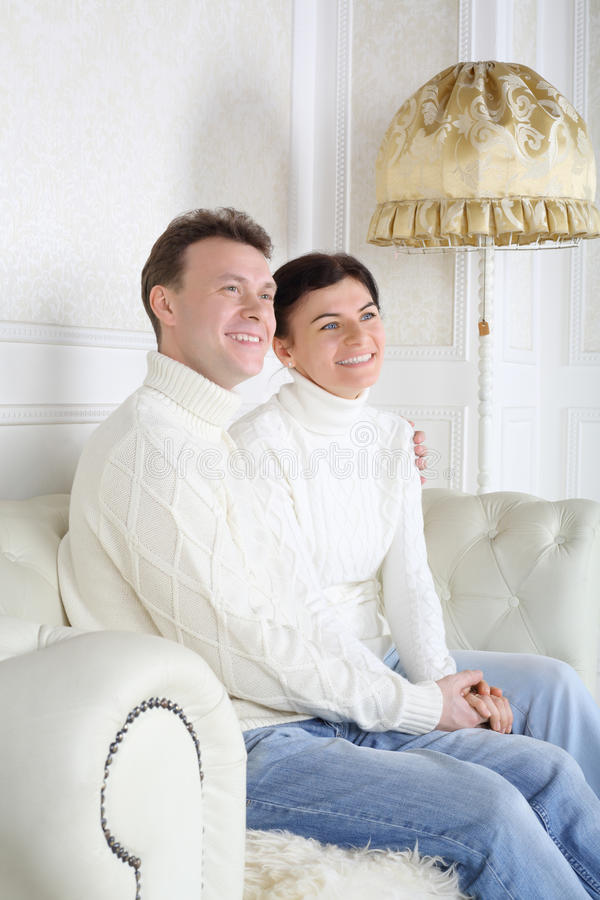 Smiling husband and wife hold hands and look away. On white leather sofa at home royalty free stock image