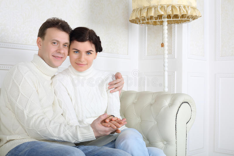 Smiling husband and wife hold hands and look at camera. On white leather sofa at home stock images
