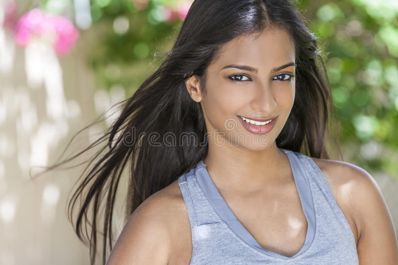 Smiling Indian Asian Woman Girl in Health & Fitness Clothing. Outdoor portrait of a beautiful Indian Asian young woman or girl outside in summer sunshine with royalty free stock photo