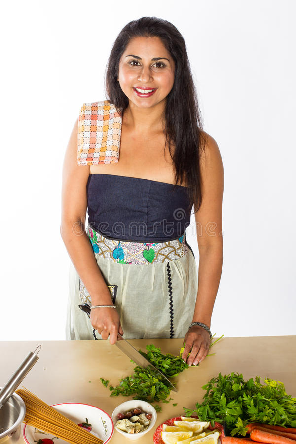Smiling Indian Chef Cuts Herbs stock photo