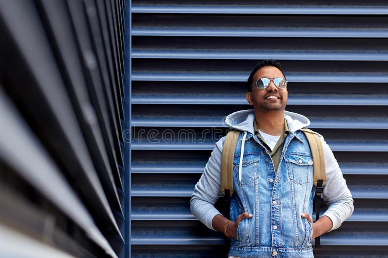 Smiling indian man with backpack on city street. Travel, tourism and lifestyle concept - smiling indian in sunglasses man with backpack on city street stock photos