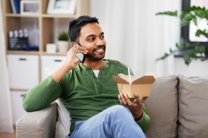 Smiling indian man eating takeaway food at home. Communication, leisure and people concept - smiling indian man calling on smartphone and eating takeaway food at royalty free stock image