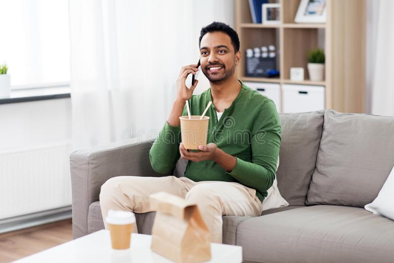 Smiling indian man eating takeaway food at home. Communication, leisure and people concept - smiling indian man calling on smartphone and eating takeaway food at stock photography