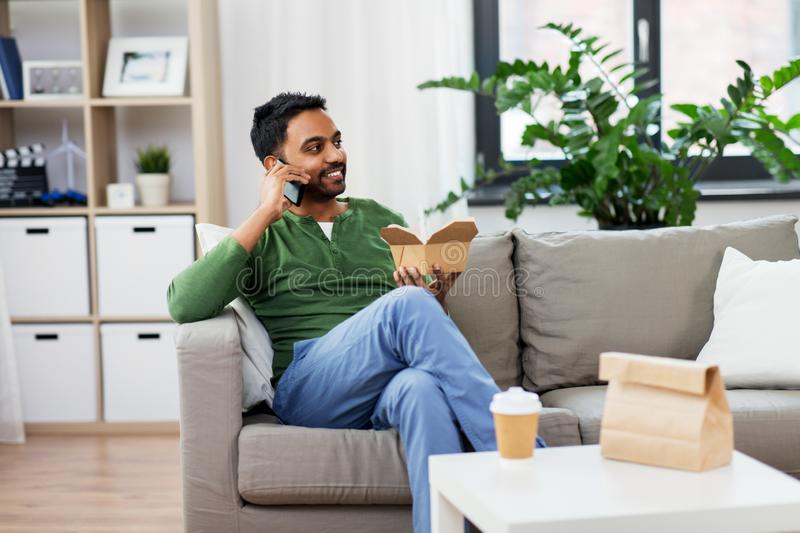 Smiling indian man eating takeaway food at home. Communication, leisure and people concept - smiling indian man calling on smartphone and eating takeaway food at royalty free stock photos