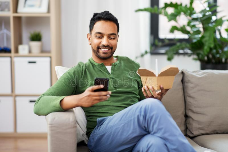 Smiling indian man eating takeaway food at home. Communication, leisure and people concept - smiling indian man using smartphone and eating takeaway food at home royalty free stock images