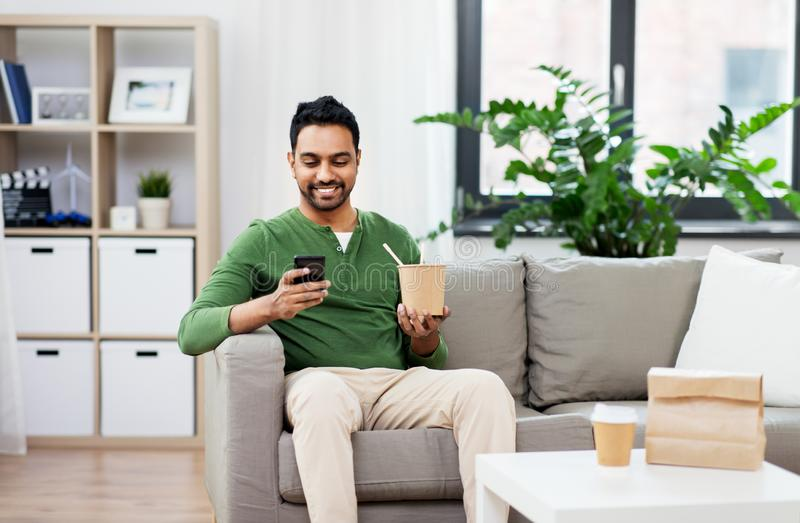 Smiling indian man eating takeaway food at home. Communication, leisure and people concept - smiling indian man using smartphone and eating takeaway food at home stock images