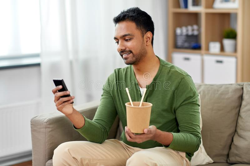 Smiling indian man eating takeaway food at home. Communication, leisure and people concept - smiling indian man using smartphone and eating takeaway food at home stock photo