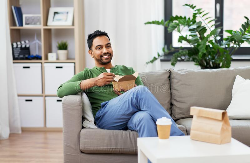 Smiling indian man eating takeaway food at home. Consumption and people concept - smiling indian man eating takeaway food at home royalty free stock photos