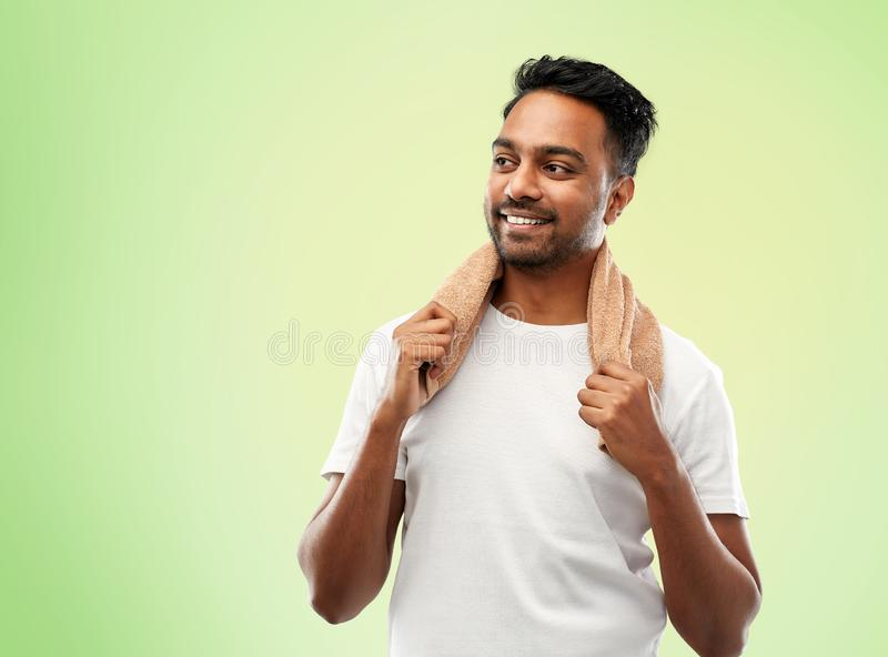 Smiling indian man with towel over green royalty free stock images