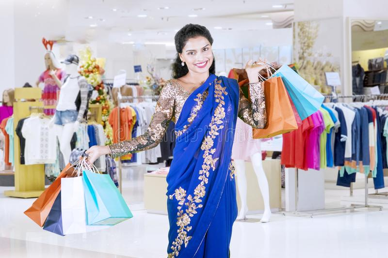 Smiling Indian woman carrying shopping bags stock images