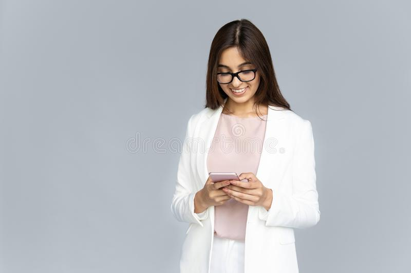 Smiling indian young business woman using phone isolated on background stock photos