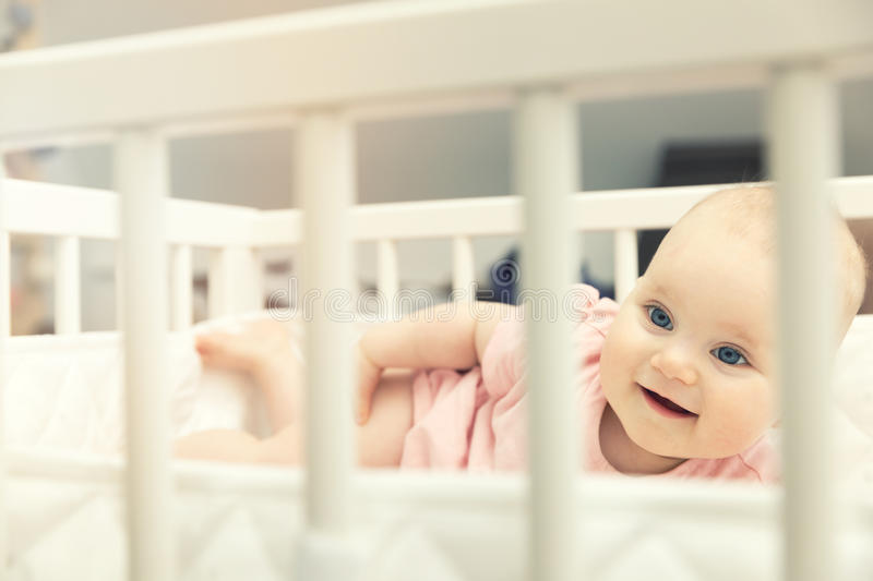 Smiling infant baby girl lying in crib at home. Smiling happy infant baby girl lying in crib at home royalty free stock images