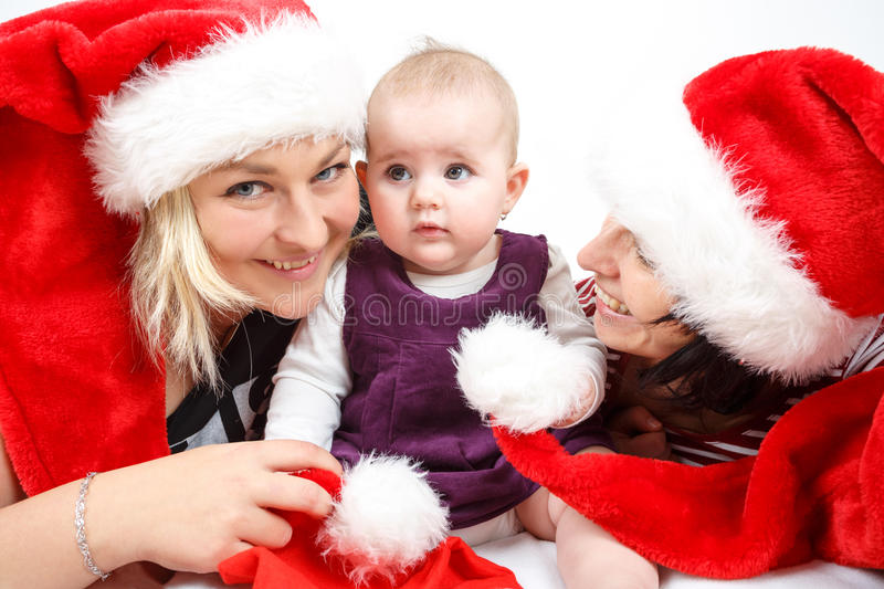 Smiling infant baby with two womans with santa hats stock photos
