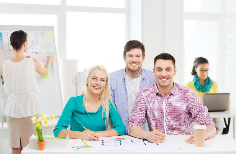 Smiling interior designers working in office. Education, interior design and office concept - smiling interior designers with color samples and blueprint in royalty free stock images