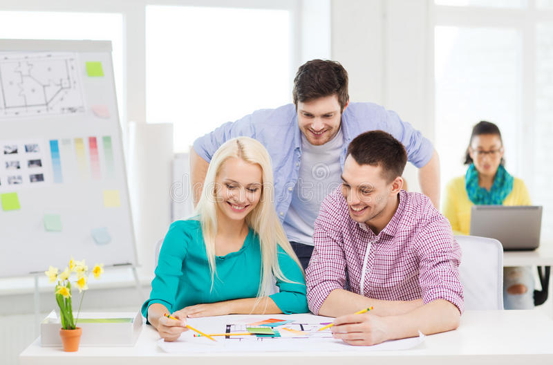 Smiling interior designers working in office. Education, interior design and office concept - smiling interior designers with color samples and blueprint in royalty free stock photography