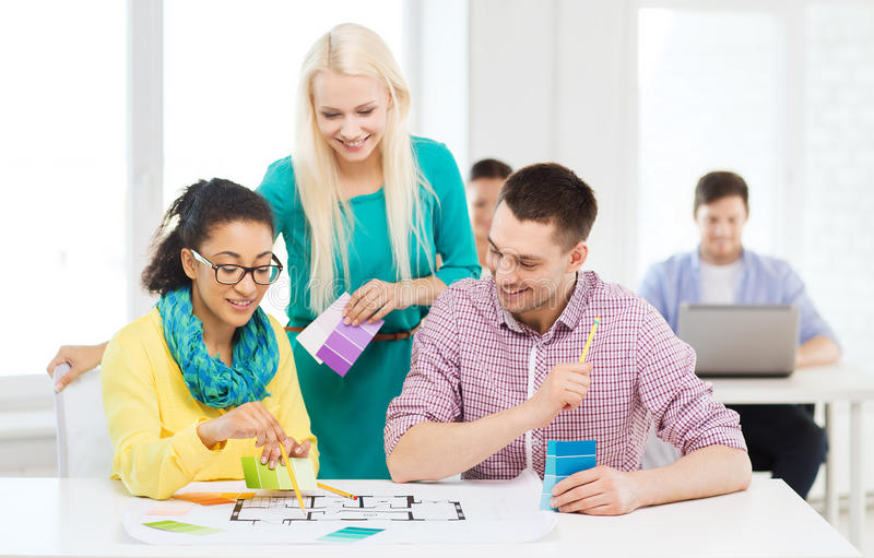 Smiling interior designers working in office. Education, interior design and office concept - smiling interior designers with color samples and blueprint in royalty free stock image
