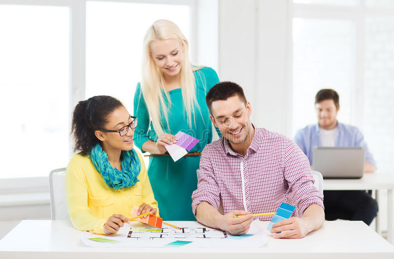 Smiling interior designers working in office. Education, interior design and office concept - smiling interior designers with color samples and blueprint in stock photo
