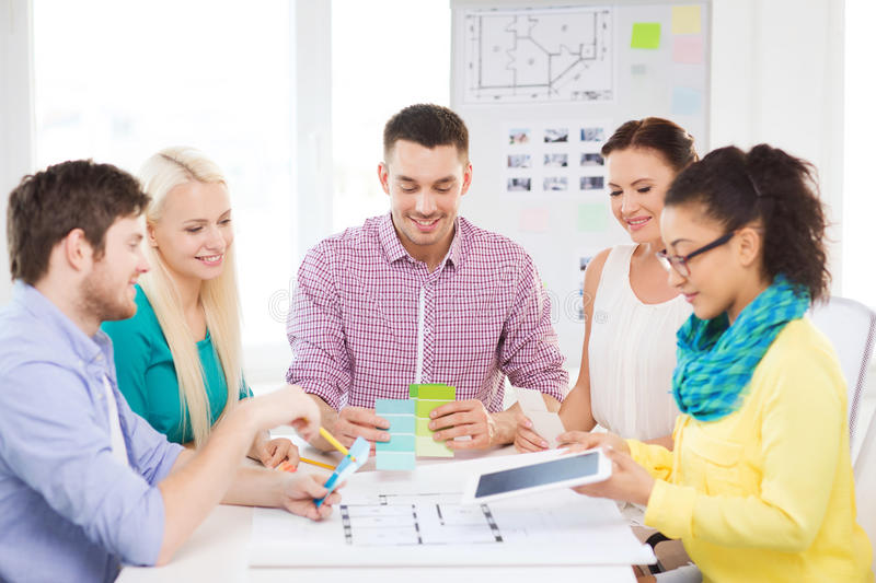 Smiling interior designers working in office. Technology, education, interior design and office concept - smiling interior designers with color samples royalty free stock images