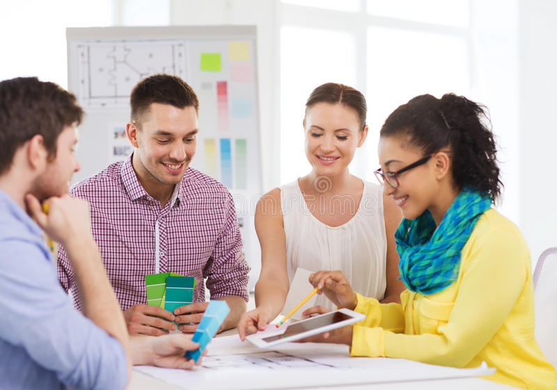 Smiling interior designers working in office. Technology, education, interior design and office concept - smiling interior designers with color samples royalty free stock image