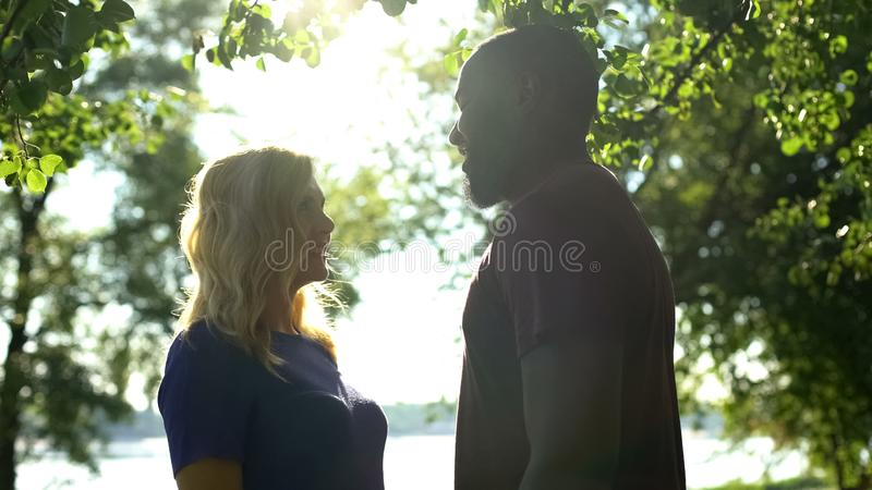Smiling interracial couple looking at each other, love despite all prejudice royalty free stock images