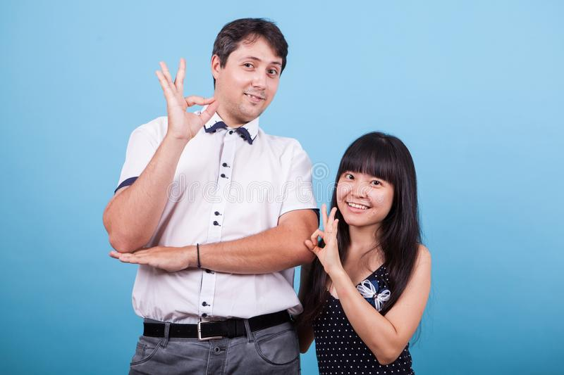 Smiling interracial couple showing ok hand gesture royalty free stock photography