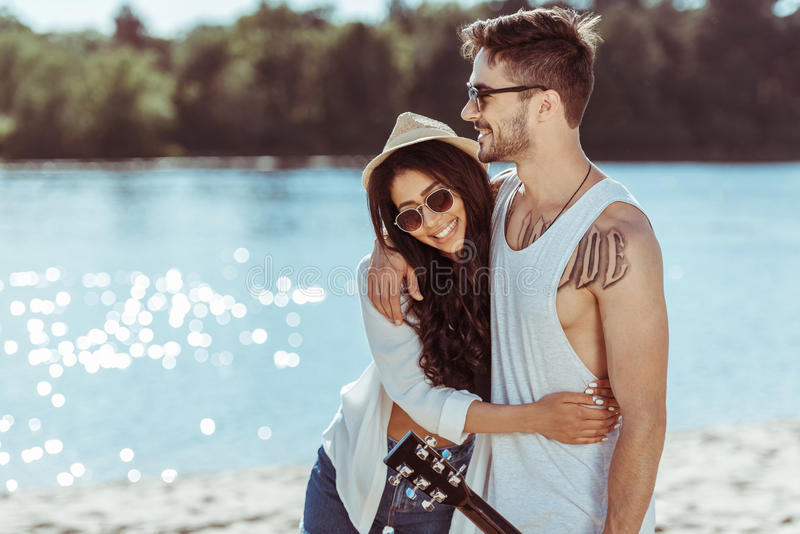 Smiling interracial couple in sunglasses embracing on riverside royalty free stock photography