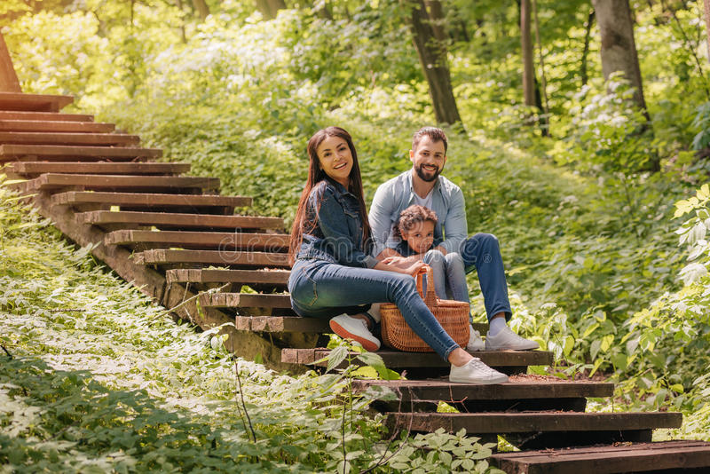 Smiling interracial family with picnic basket sitting on wooden stairs in sunny forest royalty free stock image