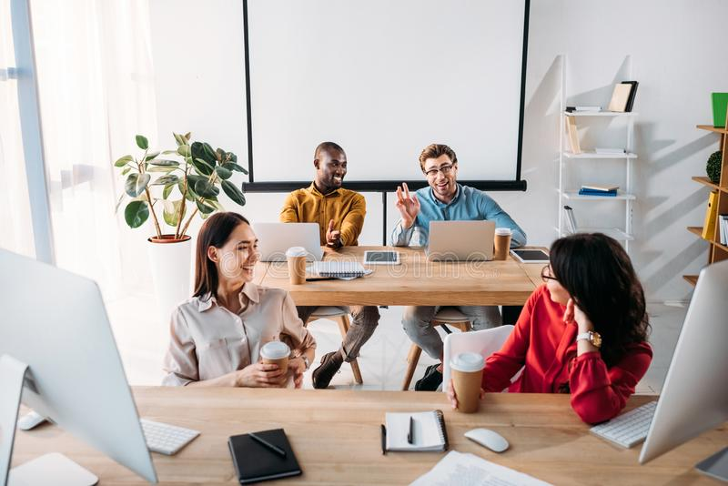 smiling interracial young business people talking during work stock images