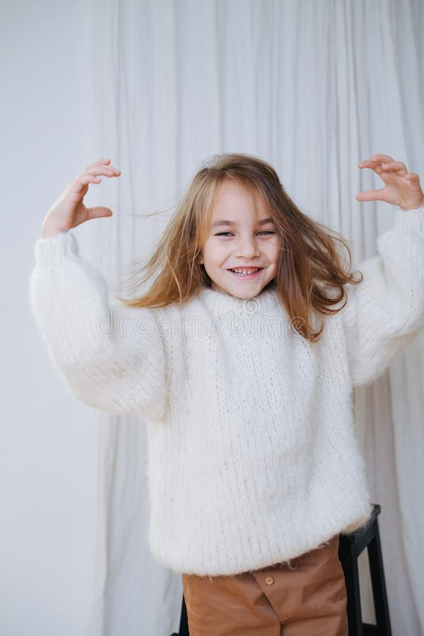 Smiling little girl with messy hair just put on white fluffy knitted sweater royalty free stock photo