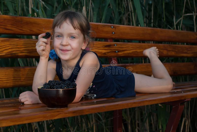 Smiling ittle girl lies on a wooden bench with a berry in her hand. royalty free stock photos