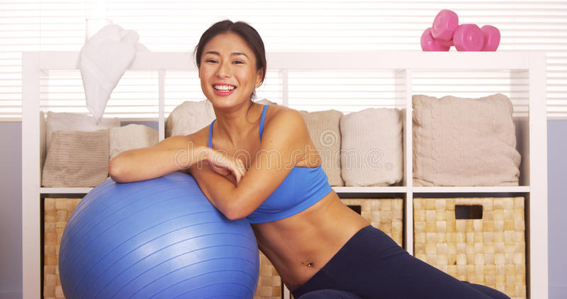 Smiling Japanese woman resting on workout ball stock photography