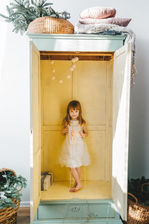 Free Smiling, Jolly, Cute Barefoot Preschool Girl With Christmas Gift Box Standing Inside Of Open Wardrobe At Home Stock Image - 193941811