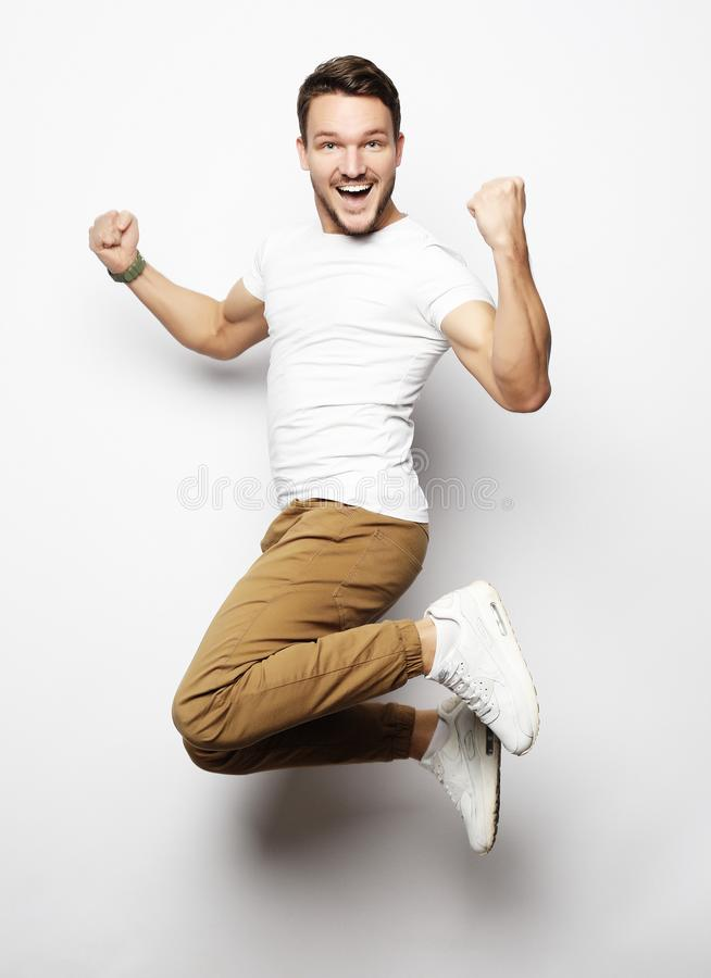 Smiling joyful man jumping on a white background. Lifestyle concept royalty free stock photos