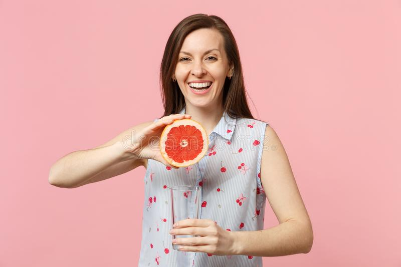 Smiling joyful young woman in summer clothes holding half of fresh ripe grapefruit glass cup isolated on pink pastel stock photography