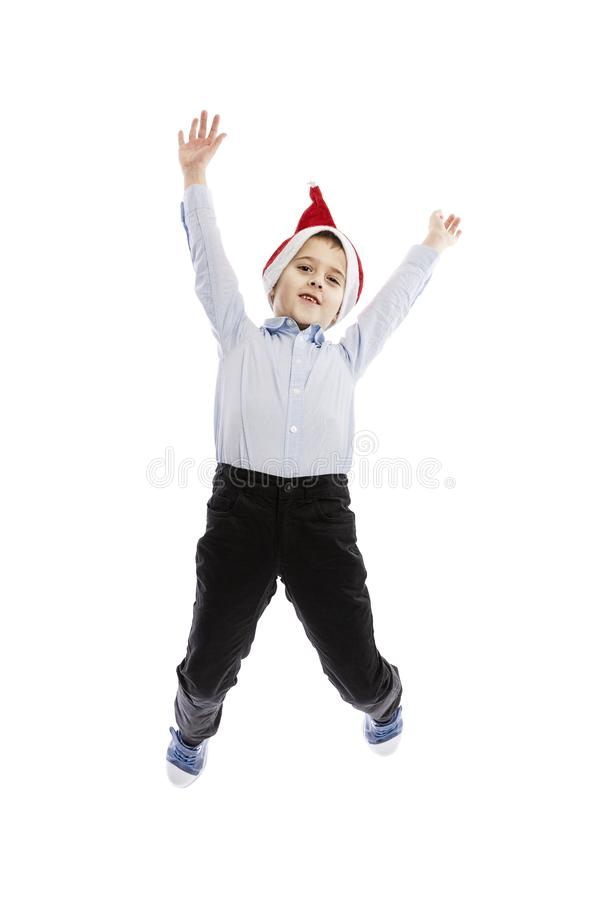 Smiling jumping schoolboy in Santa`s hat. Full height. Christmas mood. Isolated over white background. stock image