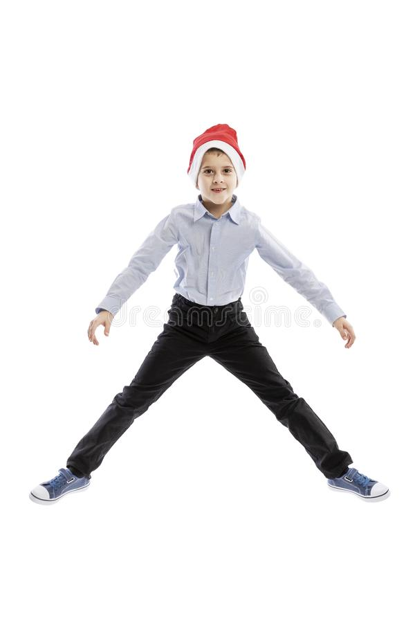 Smiling jumping schoolboy in Santa`s hat. Full height. Christmas mood. Isolated over white background. stock photo