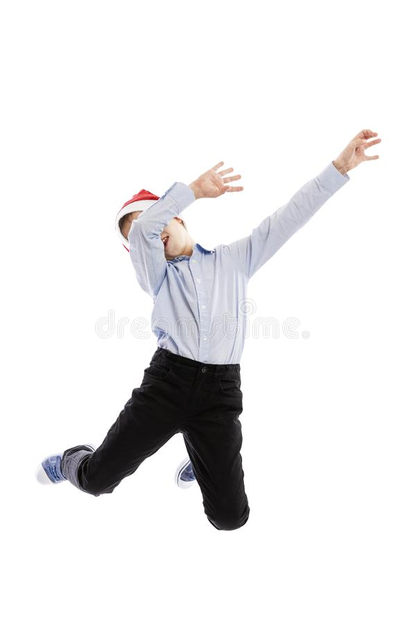 Smiling jumping schoolboy in Santa`s hat. Full height. Christmas mood. Isolated over white background. royalty free stock photos