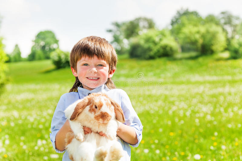 Smiling kid with cute rabbit in summer stock photography