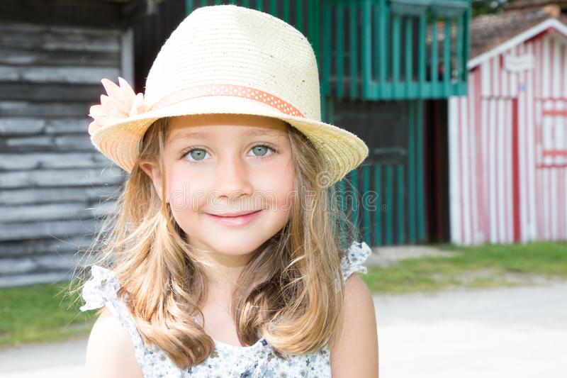 kid girl five year old posing outdoors Looking camera Childhood Closeup portrait of blonde child with straw hat stock photo