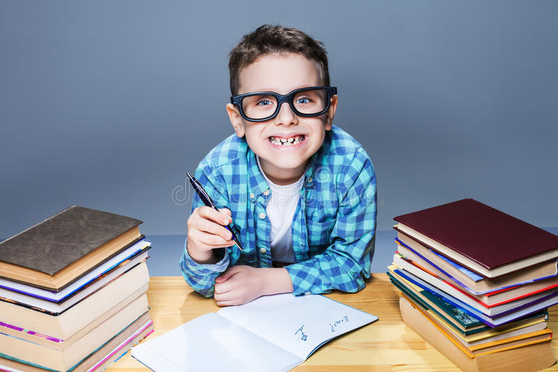 Smiling kid in glasses doing homework at the desk. Young pupil in classroom royalty free stock photo