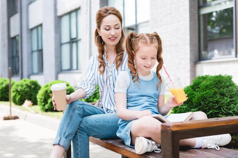 smiling kid with juice reading book with mother near by while resting on bench together stock images