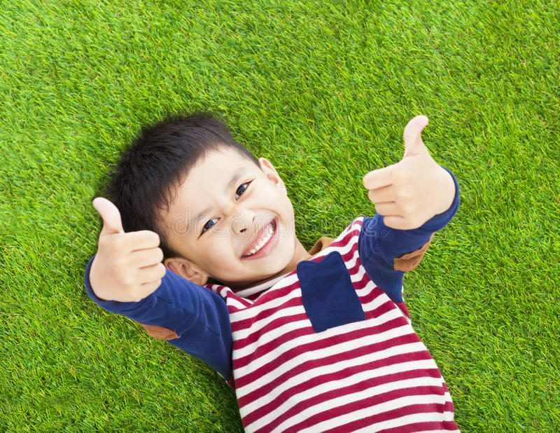 Smiling kid lying and thumb up on a meadow royalty free stock image
