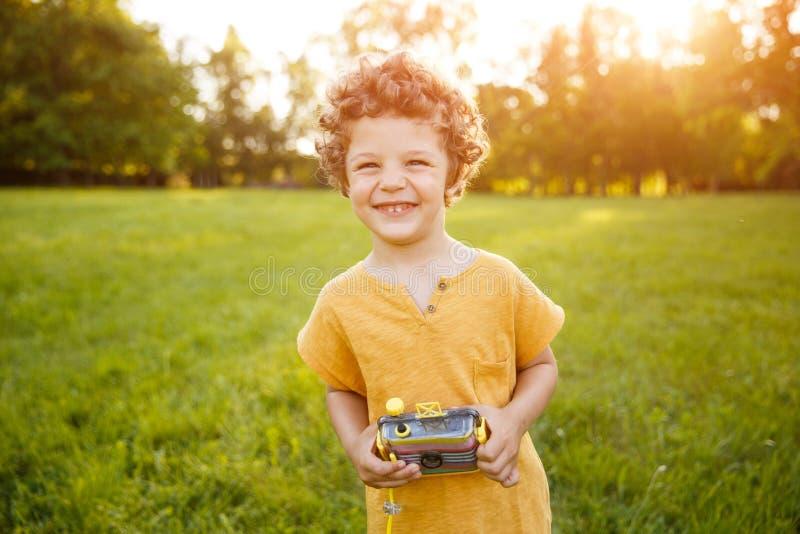 Smiling kid in orange shirt holding camera royalty free stock photos