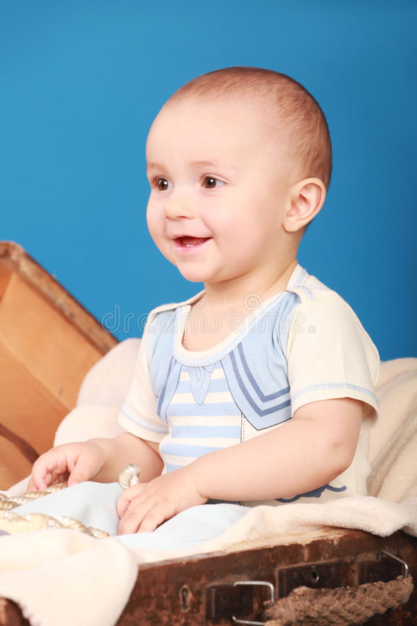 A smiling kid sits on a blue background in a sailor suit stock image