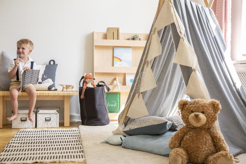 Smiling kid sitting on bench with notebook, real photo of natural playroom interior with scandinavian tent and teddy bear. Smiling kid sitting on bench with royalty free stock images