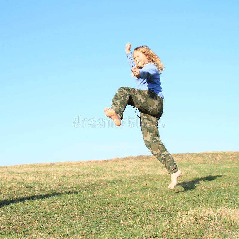Smiling girl jumping on meadow. Smiling kid - young barefoot girl with blond hair dressed in khaki pants and blue jacket jumping or crazy dancing on grass of royalty free stock photo